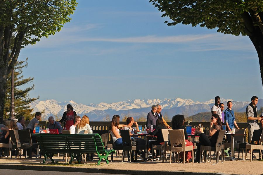 people sitting at tables with views of mountains in background