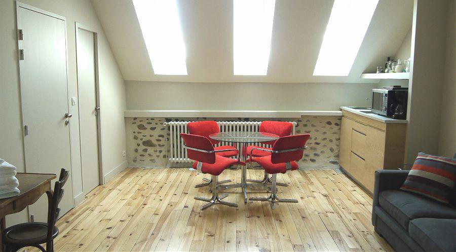 Studio de 30 m2, le coin repas avec chaises rouges et cuisinette.