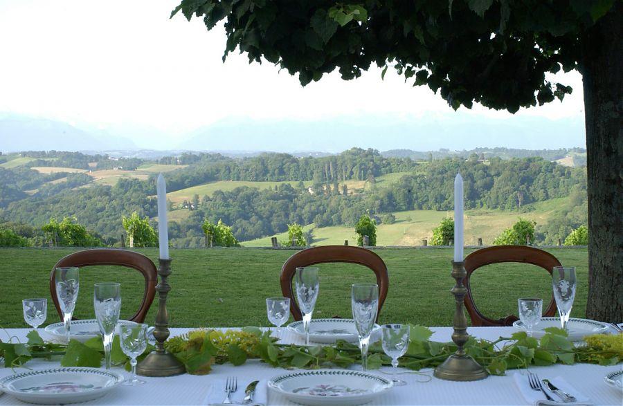 table préparée pour le dîner avec vue sur les Pyrenées en arrière-plan.