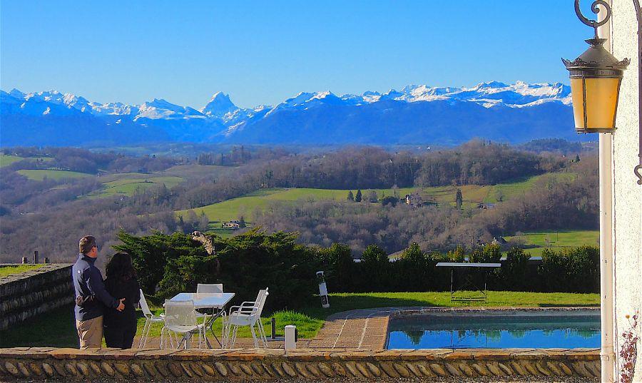 Couple, près de la piscine en regardant les montagnes . les montagnes ont de la neige sur le sommet.