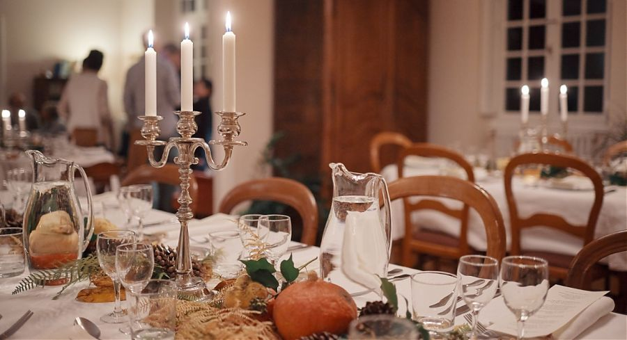 Table with candles, glasses and knives and forks.