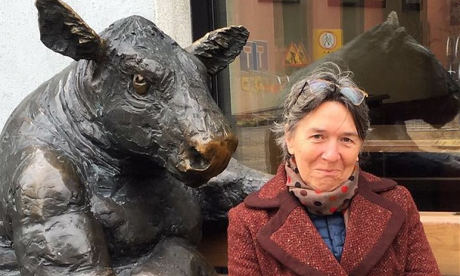 Ann kenny of clos mirabel sitting next two bronze sculpture of a bull.