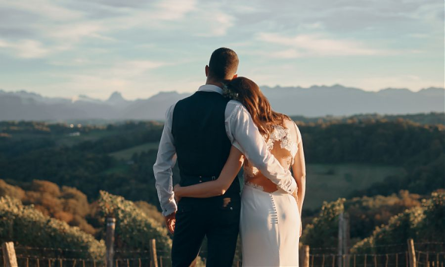 Man in waistcoat and shirt and women in wedding dress looking at mountain view from clos mirabel.