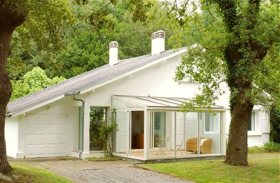 Maison blanche type bungalow, arbres.