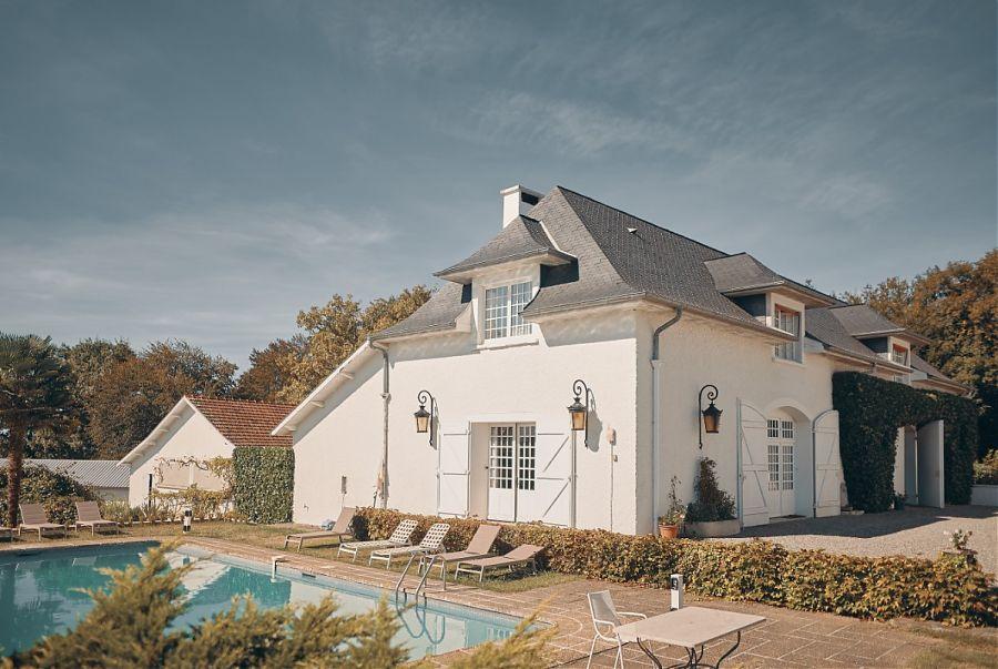 Maison blanche et piscine.