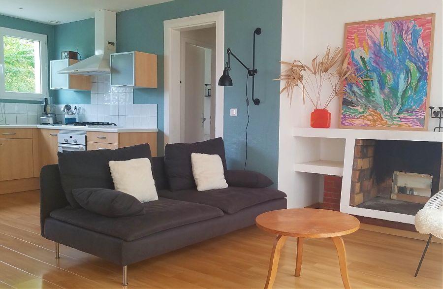 Grey sofa, blue walls, open plan kitchen lounge.