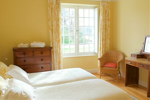 Yellow guest bedroom with twin beds and views of garden