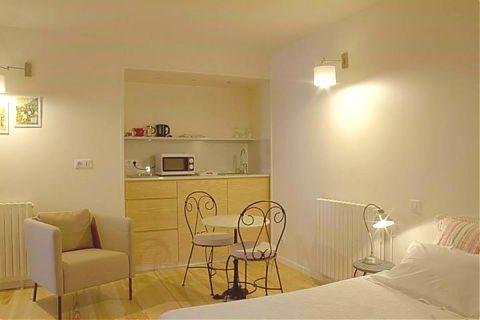 studio-chambre avec cuisinette, table, deux lits et lampe.