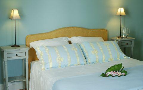 Chambre d'hôteavec un grand lit et oreillers bleus et jaunes -2 tables de chevet avec lampes.