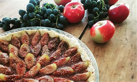 Fig tarte homemade, apples and grapes on table behind.